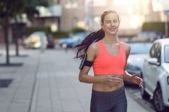 Fit young woman jogging along an urban street Stock Images