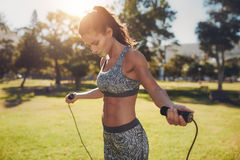 Fit young woman with jump rope in a park. Portrait of fit young woman with jump rope in a park. Fitness female doing skipping workout outdoors on a sunny day royalty free stock photo