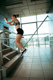 Fit young woman jumping at stair in modern interior Stock Photo