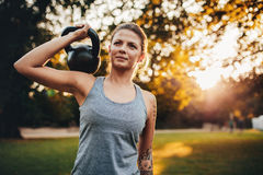Fit young woman with kettlebell weights in the park Royalty Free Stock Image