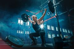 Fit young woman lifting barbells working out in a gym stock images