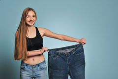 Fit young woman in loose jeans Stock Photos