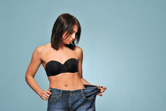 Fit young woman in loose jeans Royalty Free Stock Image