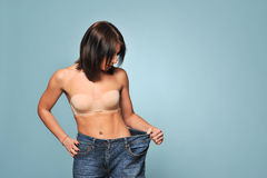 Fit young woman in loose jeans Royalty Free Stock Photography