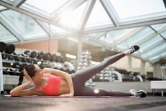 Doing gymnastics. Fit young woman lying on her right side and lifting stretched left leg during gymnastics in gym Stock Photos