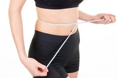 Fit young woman measures waist circumference belly after sport diet. A fit young woman measures waist circumference belly after sport diet stock photo