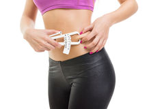 Fit young woman measuring fat on waist using caliper Royalty Free Stock Photos