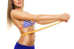 Fit young woman measuring her waist wearing bikini royalty free stock photography