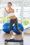 Fit young woman performing step aerobics exercise Royalty Free Stock Photo