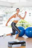 Fit young woman performing step aerobics exercise Stock Images