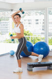 Fit young woman performing step aerobics exercise Stock Photo