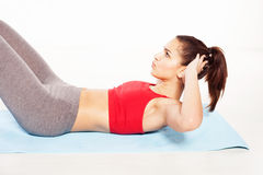 Fit young woman practicing abdominal exercises Royalty Free Stock Photography