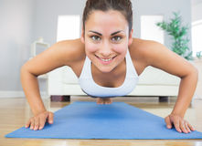 Fit young woman practicing press ups on a blue exercise mat Royalty Free Stock Images