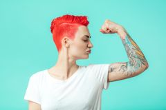 Fit young woman is proud of her braws. Glamour girl is looking at her arm`s muscles. woman likes bodybuilding royalty free stock photography