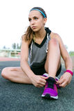 Fit young woman relaxing after run on stadium race track. Royalty Free Stock Photos