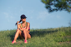 Fit young woman resting after training in park Stock Photo