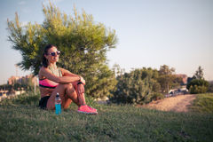 Fit young woman resting after training in park Stock Photos