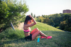 Fit young woman resting after training in park Royalty Free Stock Images