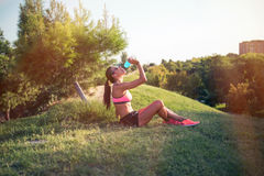 Fit young woman resting after training in park Stock Image