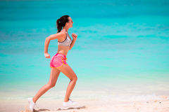 Fit young woman running along tropical beach in her sportswear Royalty Free Stock Photos