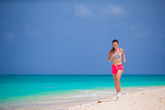 Fit young woman running along tropical beach in her sportswear Stock Photography
