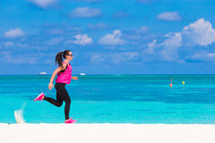 Fit young woman running along the tropical beach Royalty Free Stock Photo