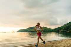 Fit young woman running on the beach during summer vacation Stock Image