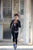 Fit young woman running outdoors Stock Photography