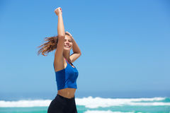 Fit young woman running by the sea with arms raised Stock Image
