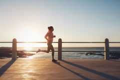 Fit and young woman running on the seaside road Royalty Free Stock Photo