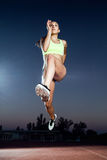 Fit young woman running on track field at night. Portrait of fit young woman running on track field at night Royalty Free Stock Image