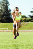 Fit young woman running on track field. Portrait of fit young woman running on track field Stock Photography