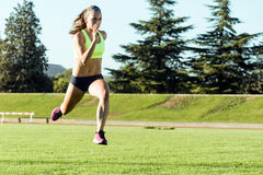 Fit young woman running on track field. Portrait of fit young woman running on track field Royalty Free Stock Photography