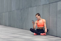 Fit young woman sitting checking her mobile Stock Photography