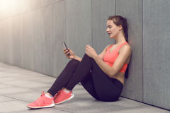 Fit young woman sitting checking her mobile Stock Photo