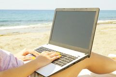 Young blonde hair woman working on laptop at the beach on sunny day. Close up of female hands typing on white notebook computer la stock photo
