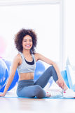 Fit young woman sitting on exercise mat in fitness studio Royalty Free Stock Photography
