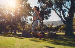 Fit young woman skipping with a jump rope in the park Royalty Free Stock Photography