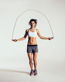Fit young woman skipping rope Stock Photos