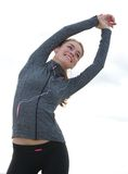 Fit young woman smiling and stretching outdoors Stock Photos