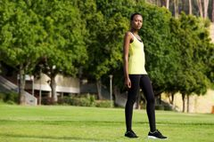 Fit young woman in sportswear standing in a park Royalty Free Stock Images
