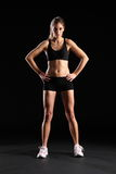Fit young woman standing in black sports outfit Stock Image