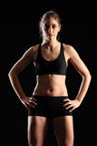 Fit young woman standing in black sports outfit. Sexy young woman wearing black sports bra and shorts, with fit, toned body. Woman facing camera with hands on Royalty Free Stock Photo