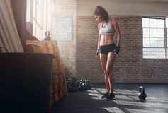 Fit and young woman standing in crossfit gym. Full length shot of fit and young woman standing in crossfit gym. Fitness female model with kettle bell on floor Royalty Free Stock Photos