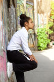 Fit young woman standing and resting outdoors. Side view portrait of a fit young african woman standing and resting outdoors after running exercise session Royalty Free Stock Images
