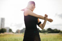 Fit young woman stretching arms at park Royalty Free Stock Images