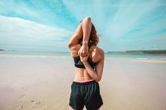 Fit young woman stretching on the beach Stock Photography