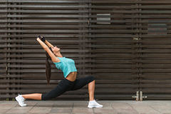 Fit young woman stretching by doing yoga low lunge exercise outdoors on the city street. Stock Photo