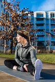 Fit young woman stretching her leg during outdoor warm-up exerci Stock Photos