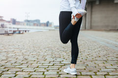Fit young woman stretching her leg before a run. Low section view of fit young woman stretching her leg before a run in city streets. Preparation for running royalty free stock image